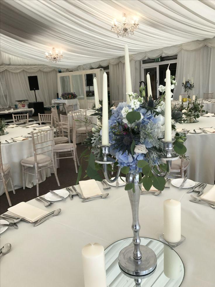 Silver Dress Candelabra: Silver Crest, Blue hydrangea, White Hydrangea, Blue Thistle, Cerise Pink Wax Flower, White Lisianthus, Eucalyptus