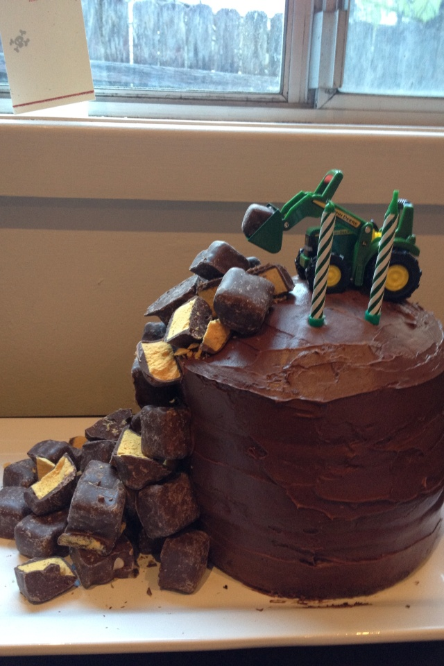 Tractor loading mini candy bars on top of cake