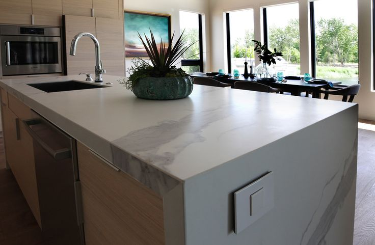 Renovare Model Home. A waterfall finish on the kitchen island counter top that also sports an outlet that disappears at a touch.