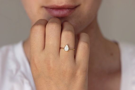 Classy solitaire pear diamond engagement ring with a beautiful 0.75 carat stone in a 18k solid gold. Clean and simple design; sparkly and impressive