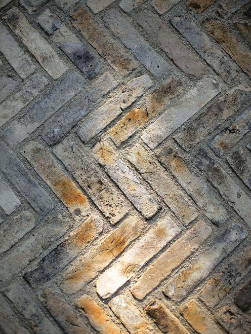 Ældre teglklinker i gul/grå nuancer lagt i sildebensforbandt. Belægning fra fortov til have/hoveddør/garage