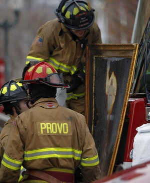 Fire Fighters marvel at the sight of a painting found in the Provo Tabernacle after the fire. Everything was burned except for Christ in the center of the painting.