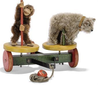 A STEIFF ROLY-DROLY MONKEY & BEAR, (1012), a brown mohair bear, brown and black glass eyes, black stitching and leather collar with chain attached to pole and a brown mohair monkey, felt face, ears, hands and feet, bead eyes, holding wooden pole, on wooden turning discs attached to a three-wheeled wagon, cord with knob and FF button, circa 1930 --8in. (20.5cm.) long (fading and general wear)