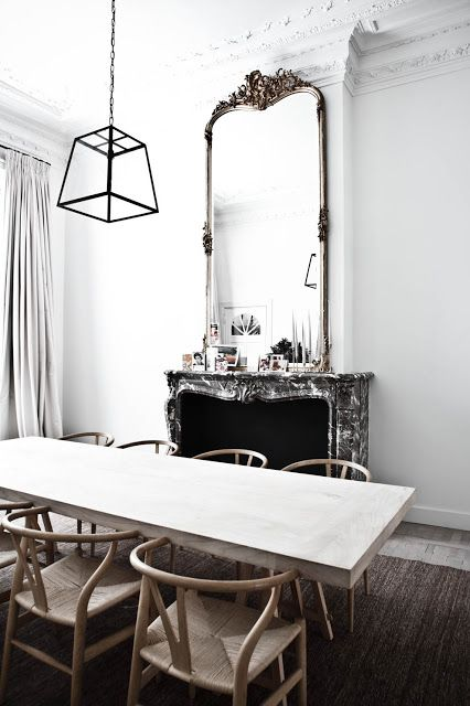 Dining room with natural wood dining table, wood floor, black pendant light, black marbled fireplace and a huge traditional mirror on the mantel
