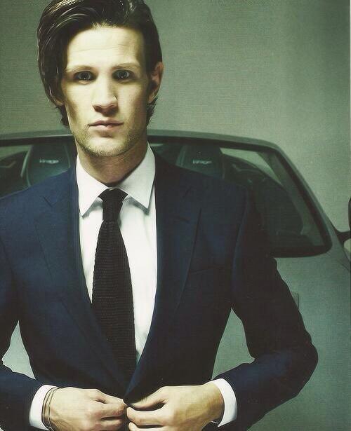 Navy suit, white shirt, black tie.