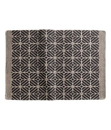 Natural white/charcoal gray. Bath mat in braided cotton fabric with printed design at front and non-slip protection at back.
