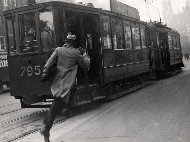 1931 - Een man probeert op volle snelheid nog een tram te halen in Amsterdam. De exacte datum van deze foto is onbekend
