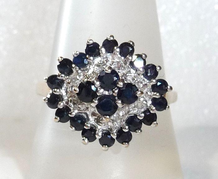 Elegant cocktail ring in 9 kt / 375 goud met 22 natuurlijke saffieren  8 diamanten ring grootte 60 / 191 mm  geen minimumverkoopprijs   Elegant cocktail ring in ruitvorm gearrangeerde gekanteld naar de vinger In de buitenste cirkel zijn 18 natuurlijke saffieren met een nacht-blauw kleur ingesteld. Dan is er een binnenste cirkel die gedeeltelijk rhodinated in witgoud. Hier 8 natuurlijke diamanten in achthoekige knippen worden gemonteerd (ik / P). Samen wegen ze 0.08 ct. In het centrum stijgt…