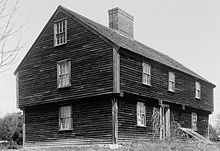 A garrison is style of house, typically two stories with the second-story overhanging in the front. The traditional ornamentation is four carved drops (pineapple or acorn shape) below the overhang. Garrisons usually have an exterior chimney at the end. Older versions have casement windows with small panes of glass, while later versions have double-hung windows. The second-story windows often are smaller than those on the first floor. Dormers often break through the cornice line.