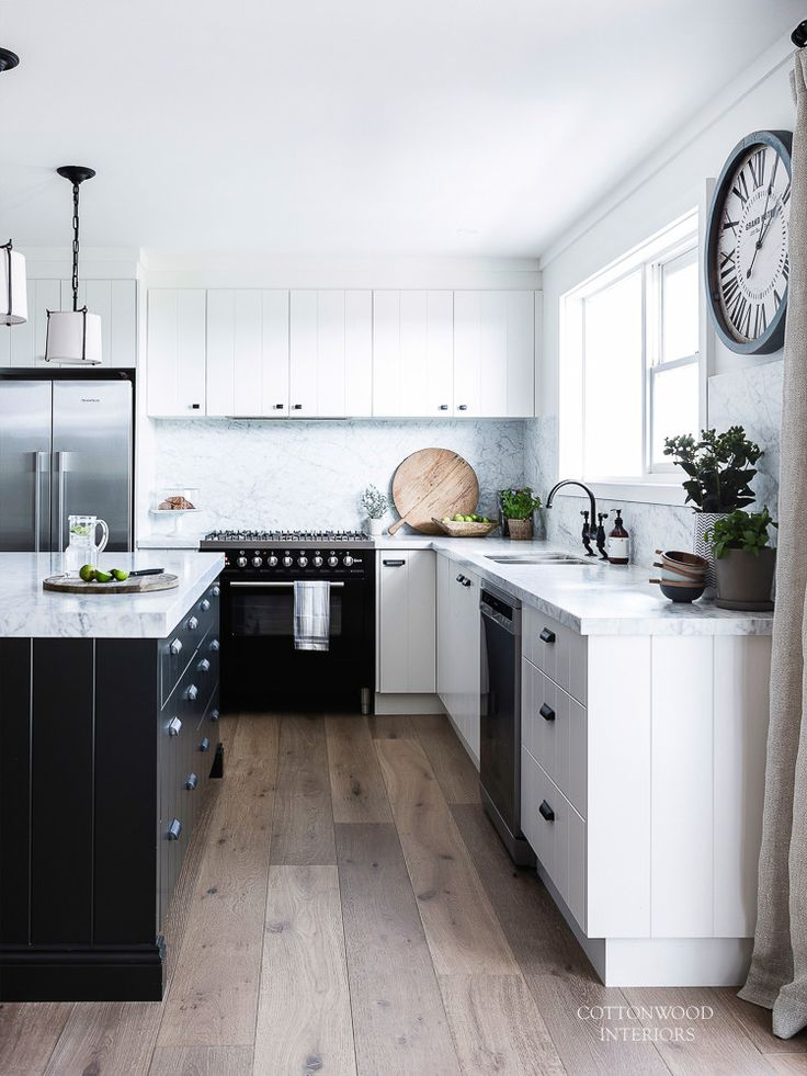 White farmhouse v-groove kitchen with black island, Carrara marble counters, American oak engineered floors. Pendants from Visual Comfort Lighting. Restoration Hardware Duluth Pulls on kitchen cabinetry | Cottonwood Interiors. Photo by Maree Homer.