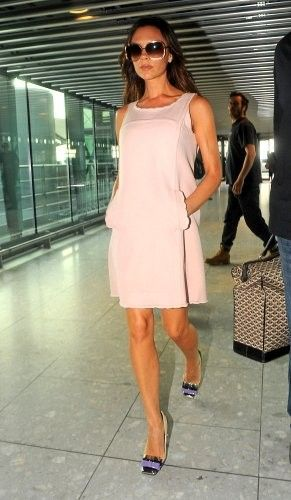 VB - in a peach dress and purple  heels as she departs Heathrow airport.   (September 7, 2010 - Source: Bauer Griffin)