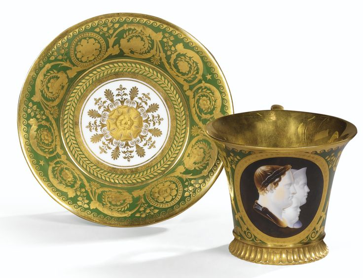 """A SÈVRES CUP AND SAUCER, """"EMPIRE"""" dated 1812, SIGNED PARANT Decorated portraits of Napoleon, Marie Louise and Aiglon painted profile bust. Cameo in a medallion is on a green background decorated with large floral scrolls and foliage, the inside of the cup and the bottom side of the saucer gold."""