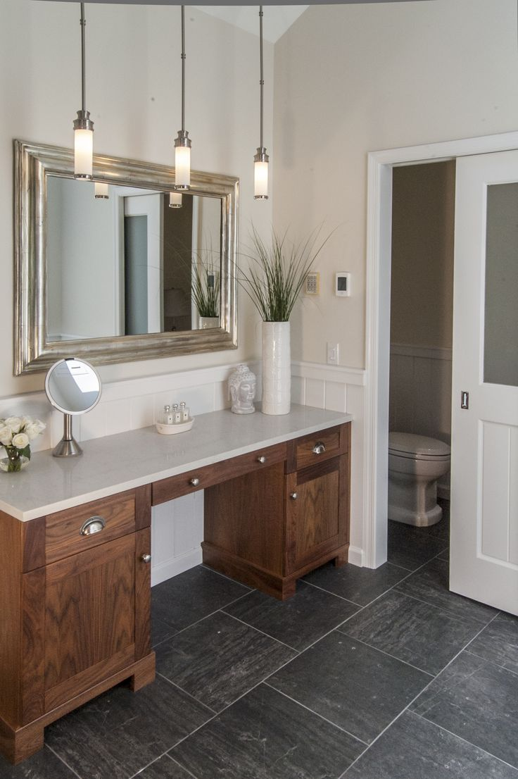 The Gardner/Fox team reconfigured the floor plan to accommodate a more spacious & luxurious master bath. The newly revamped master suite incorporates a large walk in shower with two shower heads, his & her vanities, a freestanding pedestal tub and a makeup table with pendant lighting.