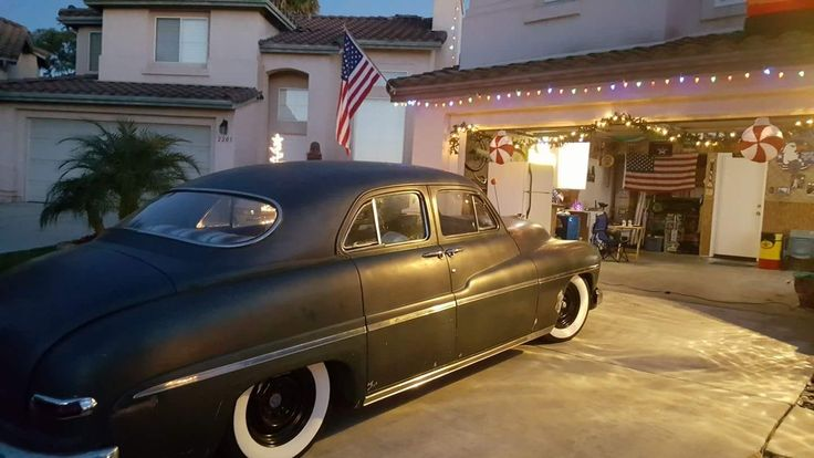 four door merc with a satin black paint job sitting on some black steal wheels and wide white wall tires vehicles mercury work pinterest wheels