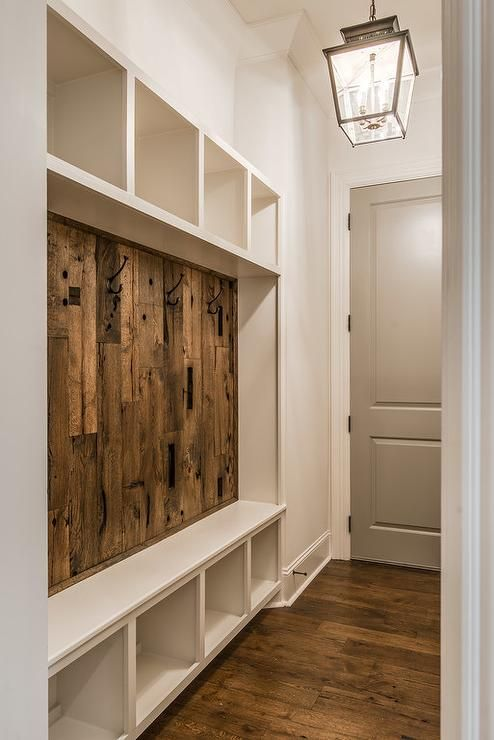 Rustic mudroom features a carriage lantern a built-in mudroom bench fitted with a barn wood backsplash sandwiched between by open shelving.
