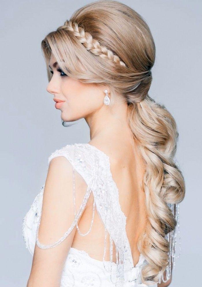 Las coletas y las trenzas combinadas también pueden ser una buena opción para las novias más clásicas. Este peinado es un buen ejemplo. Se trata de una coleta baja, con volumen y perfectamente peinada en bucles, donde el toque final lo pone una bonita trenza a modo de diadema.