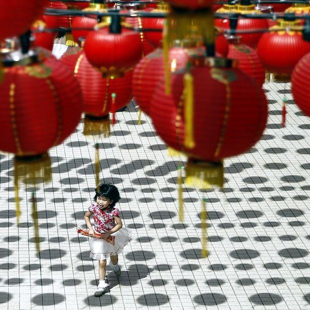 Una bambina malese di origine cinese gioca sotto le lanterne che addobbano un tempio durante i festeggiamenti per Capodanno, che è oggi secondo il calendario lunare cinese