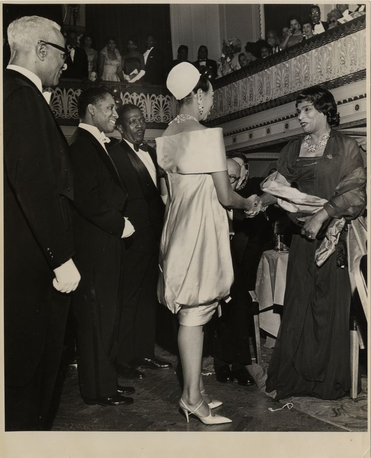 "View of singer Josephine Baker greeting Marian Anderson at the Beaux Arts Ball, Hotel Roosevelt in New York, New York. Harold Jackman on far left. Stamped on back: ""Photo by Cecil Layne."" Handwritten on back: ""Josephine Baker, Marian Anderson, Harold Jackman, extreme left, Beaux Arts Ball, Hotel Roosevelt, New York City, Feb. 12, 1960."""