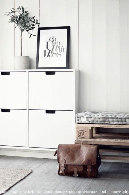 biała wisząca szafka na buty,siedzisko z drewnianej palety,pikowane poduszki w paski,białe panele na ścianie,szara podłoga z desek w przedpokoju w stylu skandynawskim