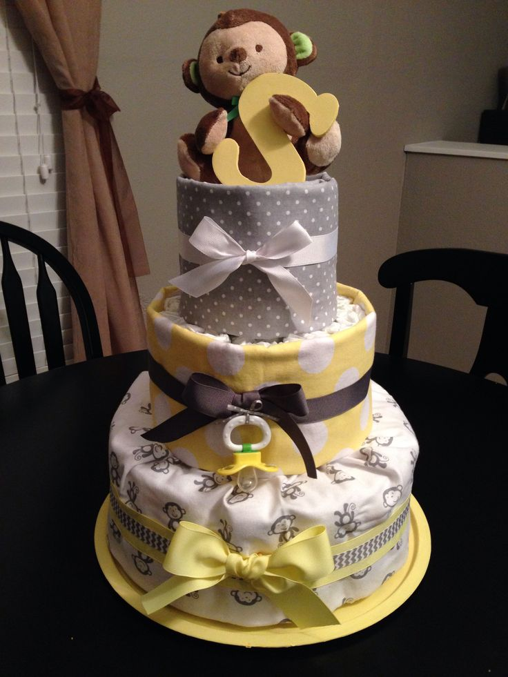 Yellow and gray diaper cake.. I love with with the receiving blankets wrapped around the diapers??