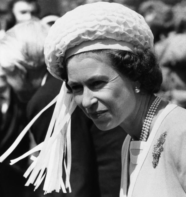 Queen Elizabeth goes for a more modern look wearing a round summer hat with cascading white ribbons in 1977. She paired her out-there headgear with a primrose yellow coat.