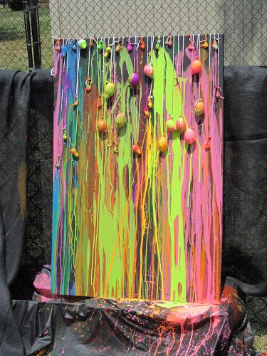 Water balloon dart painting. Need water balloons, metal darts, tempura paint, water, water bottles with sports caps, string, canvas, and drip cloth.