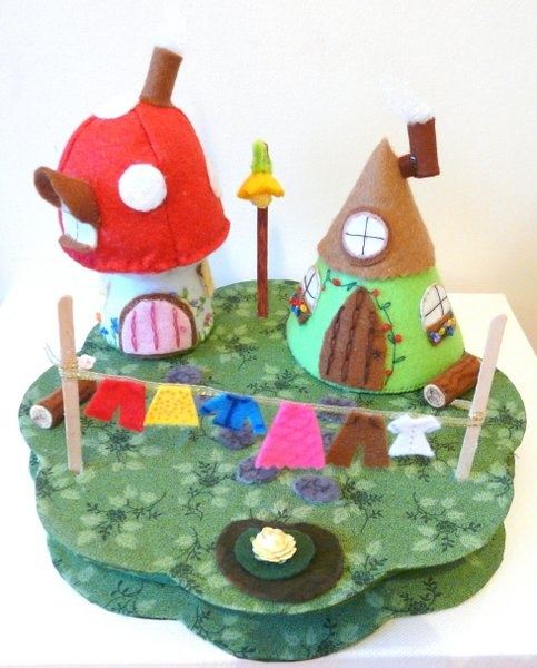 Felt handmade fairy land with toadstool house, gnome house and a flower shaped fairy lamp post. There are logs outside the houses for the little people to sit on, stepping stones, a small pond and a washing line.
