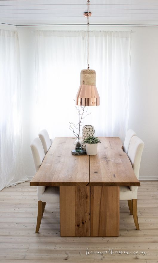 heimatbaum - photographie & design Dinning area with heavy wooden table, copper lamps from Madame Stoltz and vase from House Doctor