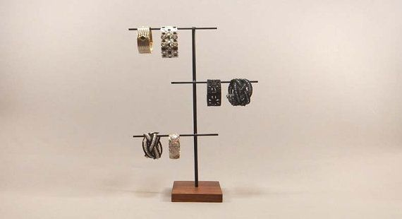 Présentoir à bijoux Ce présentoir à bijoux trois niveaux est parfait pour afficher vos bijoux spéciaux. Il dispose d'espace pour contenir des colliers, bracelets, boucles d'oreilles et montres. La base est faite de noyer noir qui a reçu plusieurs couches d'huile naturelle pour rehausser la couleur. Le support est fait d'acier qui a été coupé et soudé puis fini en peinture noire mat. L'écran entier est alors fini avec une couche transparente pour une protection supplémentaire et la…