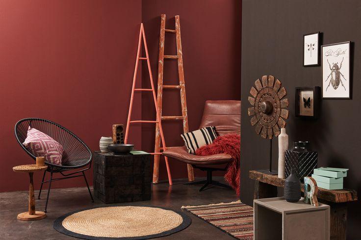 Earth & Africa: Africa meets design. De leren fauteuil is van Bodilson, het houtsnijwerk tafeltje en de tapijtloper zijn van Zuiver. De wanddecoratie met insecten is een nieuwe trend!