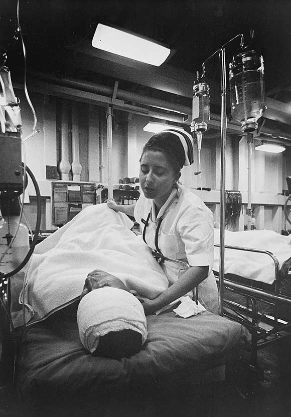 An American Navy nurse tends a patient just out of surgery in the intensive-care ward of the hospital ship U.S.S. Repose (AH-16). The ship is steaming off the coast of Vietnam, in 1967, a few miles south of the 17th parallel. U.S. Navy photo.