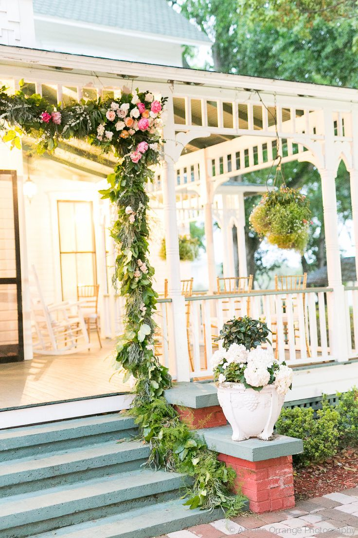 porch entryway at the historic withers maguire house is dressed with a loose and lush garland of lemon leaf, fern and weeping podocarpus, with clusters of coral charm peonies, white majolik spray roses, spirea branches, and peach, blush and pink roses.