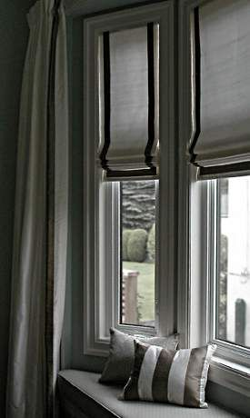 Roman style shades with contrasting but subtle dark stripes give this bay window treatment a simple and elegant designer look.