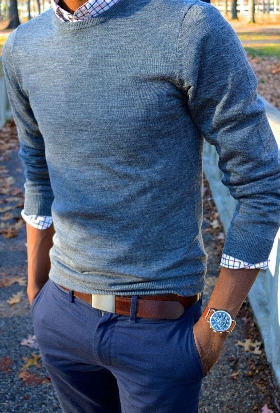 Pairing a blue crew-neck sweater with blue chinos is a comfortable option for running errands in the city. Shop this look on Lookastic: https://lookastic.com/men/looks/crew-neck-sweater-long-sleeve-shirt-chinos/18647 — White Check Long Sleeve Shirt — Blue Crew-neck Sweater — Tan Leather Watch — Brown Leather Belt — Blue Chinos