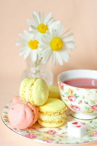 Tea:  Sunny daises and treats in lemon yellow and pastel pink brighten a floral china teacup and saucer.
