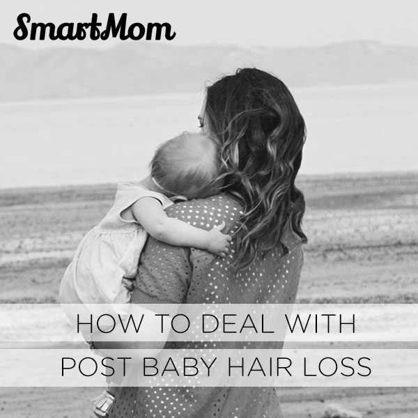 A new mother cuddles her baby while dealing with post baby hair loss.