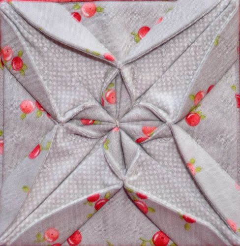 Closeup Block type:log cabin Block size:11 inches Colour scheme:reds and neutrals Texture/fabric manipulation:fabric folding / fabric origami Quilt size:The finished quilt is 52 1/2 x 52 1/2.…