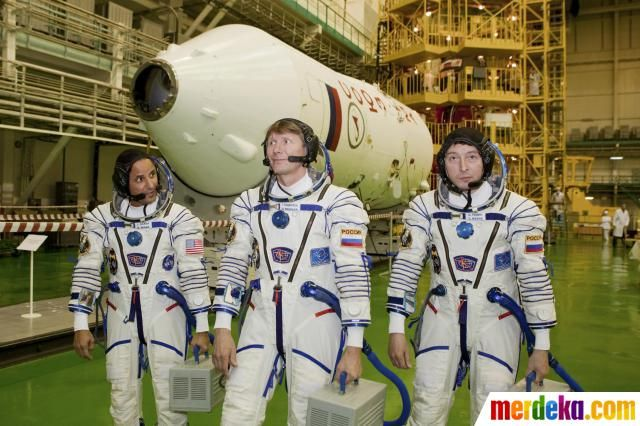 Awak International Space Station (ISS) astronot dari AS Joseph Acaba (kiri) dan kosmonot Rusia Gennady Padalka (tengah) dan Sergei Revin berpose di dekat pesawat ruang angkasa Soyuz di kosmodrom Baikonur.