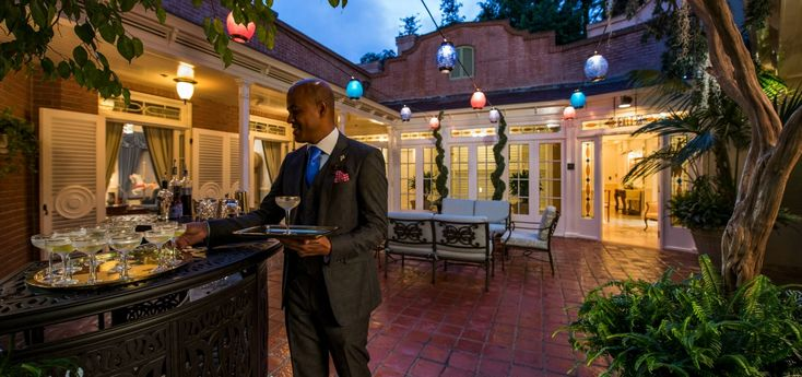 One of 21 Royal's professional butlers, dressed in suit and tie, places drinks on his tray beneath glowing lanterns on the outdoor patio