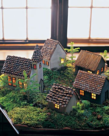 Holiday Village: These basewood buildings are painted to look old and weathered. Birch twigs make door and window frames, and the church even has birch doorknobs. Three houses and the church are shingled with pinecone scales, while the rear house has a pine-needle roof. The ground is covered with moss and balsam sprigs; a little path, made from pink granite pebbles, rambles through the village.