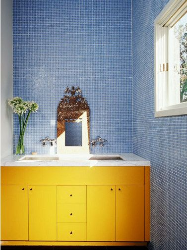 Lovin' the contrast of the blue tiles and yellow cabinets.  Plus the simple decorative touches add a little something special!