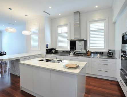 Stunning new kitchen with jarrah floorboards offset against a classic white cupboards with beautiful stone bench-tops and feature lighting.