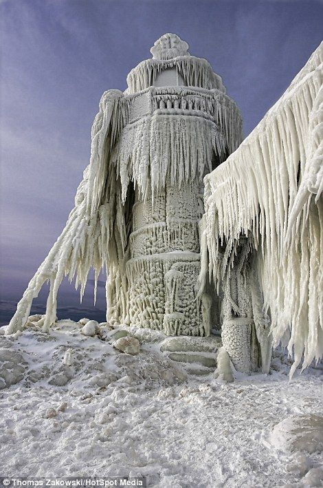 A lighthouse stands frozen still after a big storm in St Joseph, Michigan.  Thomas Zakowski is the photographer who captured these beautiful images of the frozen lighthouses.