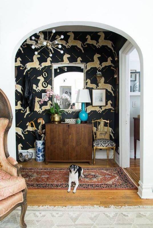 Eclectic entryway with a zebra wallpaper, a sputnik chandelier, and a vintage dresser