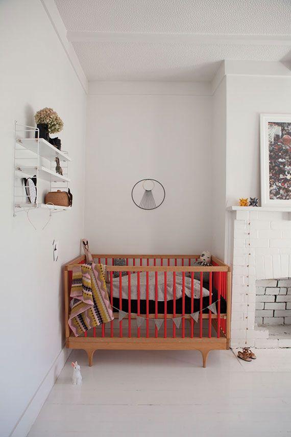 modern nursery with wood & red crib, weaving wall hanging, fireplace