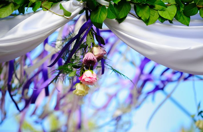 Hanging ribbons and  flowers in shades of lavander and purple for the ceremony. Designed by Dream Bloom and photos by Glen Cabotage