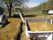 After all of the walls are leveled and squared, a six inch concrete footing is poured to anchor the walls in place.