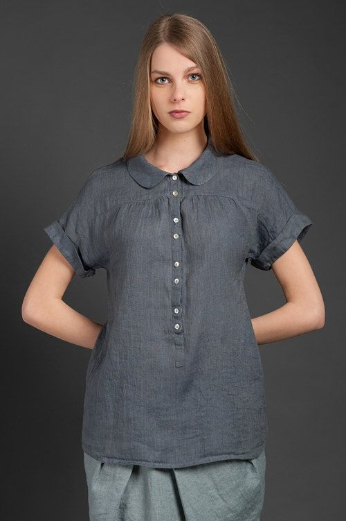 Dark asphalt grey 100% linen summer blouse with a row of white buttons at the front. Made from lightweight, thin, specially washed fabric, thus it is shrink-resistant, and doesn't require any ironing. It features a Peter Pan collar, short folded sleeves, and slight pleats above the chest, which make the blouse even more flattering and elegant. This thin hip-length garment will be just perfect on a hot summer day, but also suitable for cooler weather when worn under a jacket or sweater…