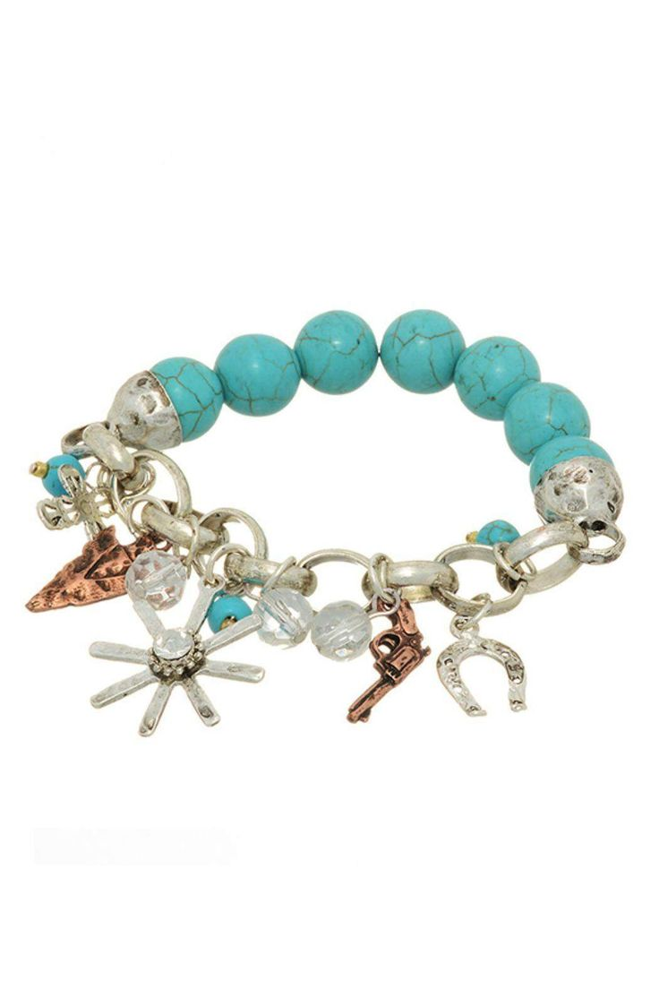 Burnished silver tone stretch bracelet featuring turquoise natural stone beads with a cluster of western themed charms. They include a spur with rhinestone, copper arrow head, silver horse shoe, copper handgun, and a silver cross. This bracelet will look great with about anything, but if you want to really stand out in the crowd, slip on your jeans, boots, and cowboy hat for some boot-scootin' boogie!   Western Turquoise Bracelet by Mimi's Gift Gallery. Accessories - Jewelry - Bracelets…