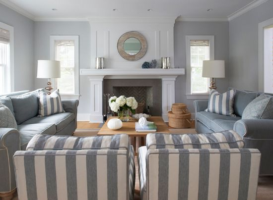 furnature layout.  striped chairs.  comfortable.  gorgeous fireplace.
